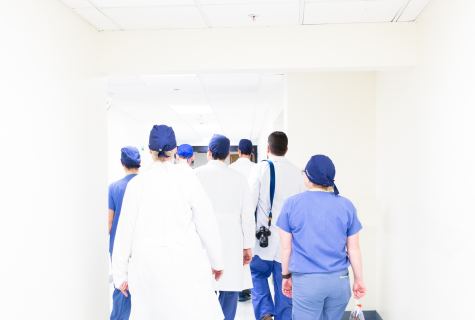 A group of doctors walks away down a corridor